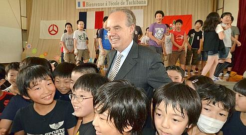 French Culture Minister Frederic Mitterrand (C) is surrounded by pupils as he visits the Tachibana elementary scholl in Koriyama city in Fukushima prefecture, 50km west of a stricken nuclear plant, on July 14, 2011 on the French national day. Mitterannd is on a three-day visit to Japan. AFP PHOTO / Yoshikazu TSUNO